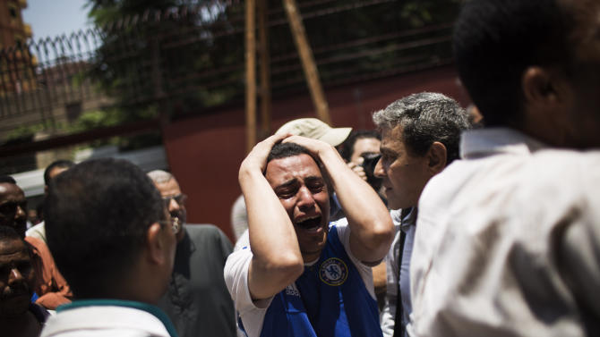 An Egyptian man cries outside a morgue after carrying the corpse of his brother killed near the Republican Guard building in Cairo, Egypt, Monday, July 8, 2013. Egyptian soldiers and police opened fire on supporters of the ousted president early Monday in violence that left dozens of people killed, including one officer, outside a military building in Cairo where demonstrators had been holding a sit-in, government officials and witnesses said. (AP Photo/Manu Brabo)