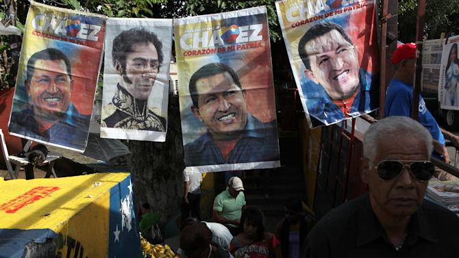 People walk by election campaign posters of President Hugo Chavez and a picture of independence hero Simon Bolivar in Caracas, Venezuela, Saturday, Oct. 6, 2012. Chavez is running for re-election against opposition candidate Henrique Capriles in Sunday's presidential election. (AP Photo/Rodrigo Abd)