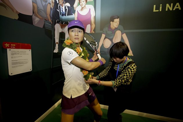 A woman puts a garland onto a wax figure of Chinese tennis player Li Na at the Madame Tussauds Museum in Wuhan in central China's Hubei province Satur...