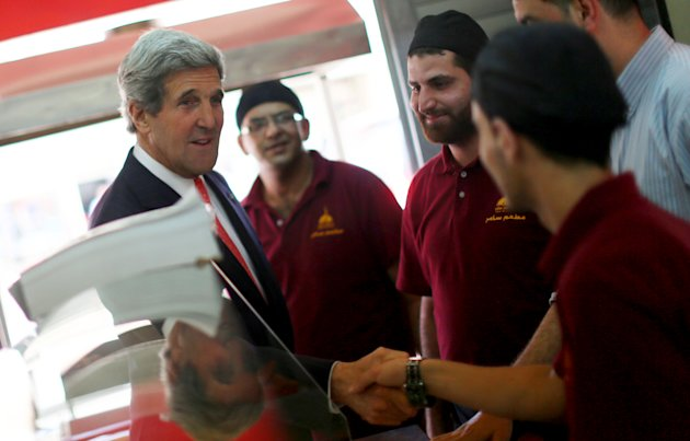 U.S. Secretary of State John Kerry shakea hands with Palestinian restaurant employees as he stops by for a snack after his meeting with Palestinian President Mahmoud Abbas in the West Bank city of Ram