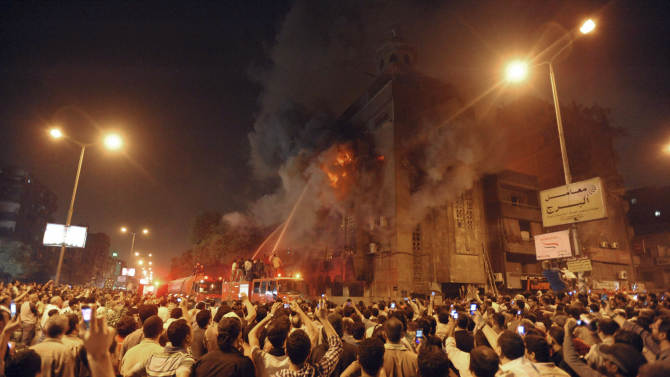 FILE -- In this May 7, 2011 file photograph, firemen fight a fire at a church surrounded by angry Muslims in the Imbaba neighborhood in Cairo, Egypt . Christians and Muslims fought in the streets of western Cairo in violence triggered by word of a mixed romance. Tribal sheiks and lawmakers agreed to reverse a decision to expel eight families from Egypt's northern province of Alexandria and allow five of the families to return to the town after clashes erupted over an alleged love affair between a Christian man and a Muslim woman, a rights activist said Friday.(AP Photo,File)