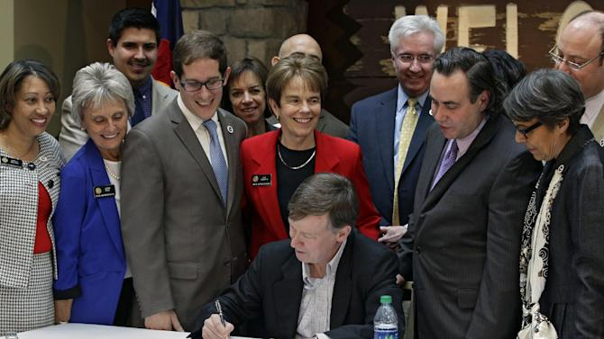 Colorado Gov. John Hickenlooper is surrounded by member of the State Legislature as he signs the Civil Unions Act into law at the Colorado History Museum in Denver, Colo., on Thursday, March 21, 2013. (AP Photo/Brennan Linsley)