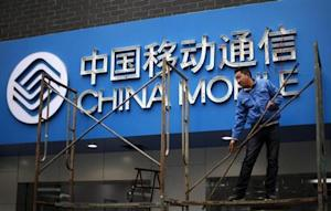 A labourer works in front of a sign for China Mobile at the company's office in downtown Shanghai