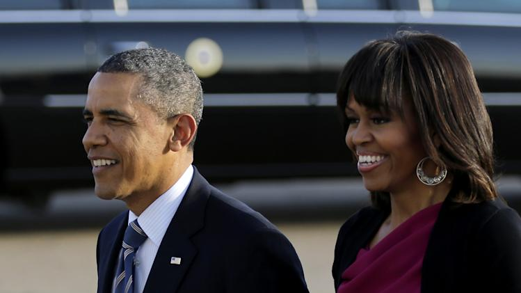 President Barack Obama and first lady Michelle Obama walk over to greet guests who awaited for them to arrive at Love Field Wednesday, April 24, 2013, in Dallas. The President will be in attendance Thursday at the George W. Bush presidential library dedication.  (AP Photo/Tony Gutierrez)