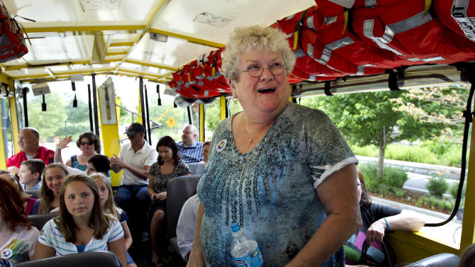 FILE - In this June 28, 2012 file photo, bus monitor Karen Klein, of Greece, N.Y., is surrounded by school children while riding a tourist duck boat, an amphibious vehicle, in Boston. Klein who was shown in a video being relentlessly bullied by a group of boys says she's retiring. She tells The Associated Press Friday, July 27, 2012 that her decision to leave the job she held for three years was tough but that it's time to move on.  (AP Photo/Steven Senne, File)
