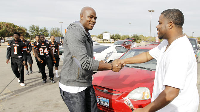 Dallas defensive lineman DeMarcus Ware, left, leads the captains of the Lancaster Tigers high school football team around town to drum up support among the residents for their upcoming playoff game during the Duracell Trust Your Power NFL Campaign event on Tuesday, Nov. 13, 2012 in Lancaster, Texas. (Photo by Brandon Wade/Invision for Duracell/AP Images)