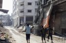 Members of Free Syrian Army walk along damaged street filled with debris in Homs