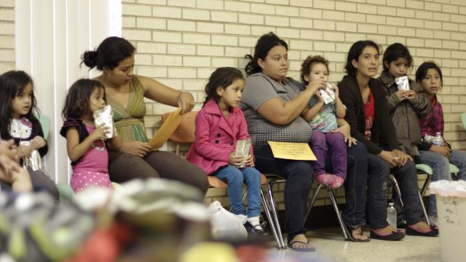 Migrants sit at the Sacred Heart Catholic Church temporary migrant shelter in McAllen, Texas