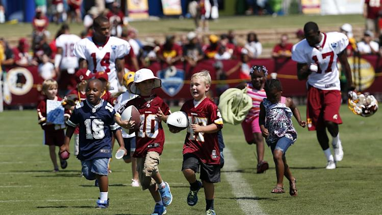 Children run with Washington Redskins receivers Ryan Grant  (14), and Rashad Lawrence (17) after practice at the team's NFL football training facility, Friday, July 25, 2014 in Richmond, Va. (AP Photo)