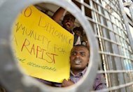 Indian activists from 'Campaign Against Child Labour' hold posters and shout slogans after they were arrested during a demonstration in Bangalore, on June 18, 2012. The Indian wife of a French consular official charged with raping their daughter has demanded a meeting with Francois Hollande, presenting the French president with a thorny diplomatic dilemma on his first state visit to India