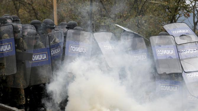 Macedonian police officers try to take cover from tear gas thrown back by a stranded migrant, as minor clashes broke out during a protest against the building of a metal fence at the Greek-Macedonian borders near the village of Idomeni