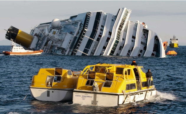 Investigators approach the luxury cruise ship Costa Concordia which leans on its starboard side after running aground in the tiny Tuscan island of Isola del Giglio, Italy, Sunday, Jan. 15, 2012. The C