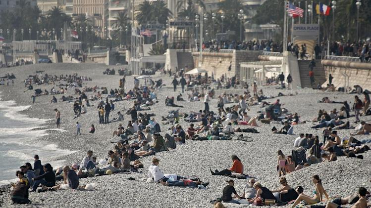 People sunbathe on the beach of Nice, southeastern France, Sunday, March 9, 2014. Temperature rose to 20 degrees Celsius (68 Fahrenheit). (AP Photo/Lionel Cironneau)