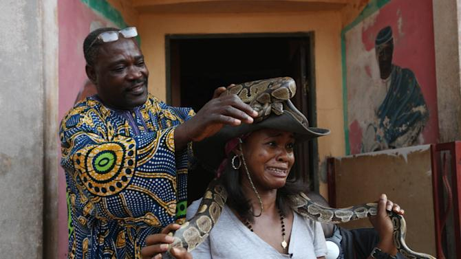 Aduare Achumba, a visitor to the Temple of Pythons, reacts as a guide puts a python on her head in Ouidah, Benin, on Wednesday, Jan. 9, 2013. Ouidah, considered the major cultural city in the West African nation of Benin, is preparing for its annual Voodoo Festival on Thursday. Voodoo is an official religion in this nation of 9 million people and this year's festival will honor the salves taken from surrounding countries and sent into America and the Caribbean, people who brought the religion with them. (AP Photo/Sunday Alamba)