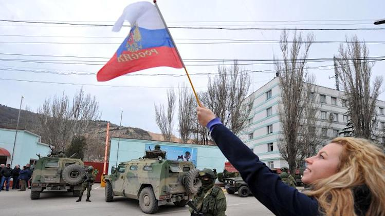 A pro-Russian supporter waves a Russian flag in front of pro-Russian armed men in military fatigues blocking the base of the Ukrainian frontier guards, in Balaklava, a small city not far from Sevastopol, on March 1, 2014