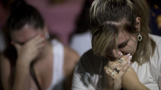 Women react during a march near the Kiss nightclub honoring the victims of early Sunday's fatal fire inside the club in Santa Maria, Brazil, Monday, Jan. 28, 2013. All the elements were in place for the tragedy at the Kiss nightclub early Sunday. The result was the world's worst fire of its kind in more than a decade, with 231 people dead and this southern Brazilian college town in shock and mourning.(AP Photo/Felipe Dana)