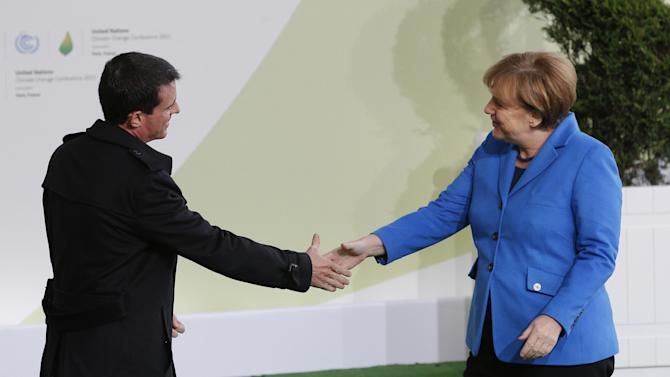 German Chancellor Angela Merkel, right, is greeted by French Prime Minister Manuel Valls as she arrives for the COP21, United Nations Climate Change Conference, in Le Bourget, outside Paris, Monday, Nov. 30, 2015. (AP Photo/Christophe Ena, Pool)
