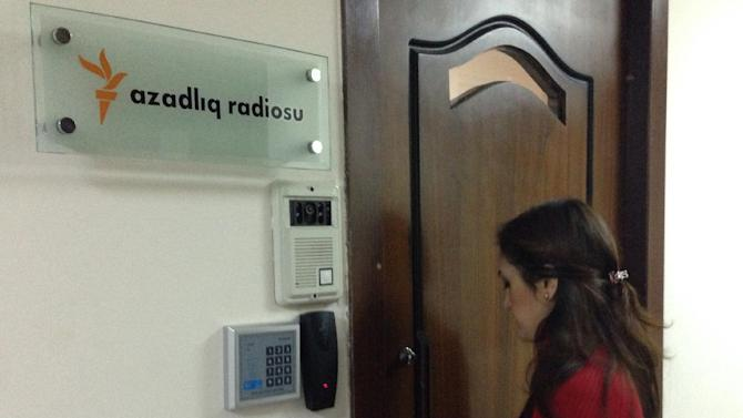 A journalist enters Radio Free Europe headquarters in Baku, Azerbaijan Friday, Dec. 26, 2014. The radio station funded by the U.S. government says its office in Azerbaijan's capital of Baku has been raided by prosecutors who claim to have a court decision to shut it down. Radio Free Europe/Radio Liberty on Friday quoted the director of its Azerbaijani service saying that the office has been locked down since early morning by prosecutors and armed police. (AP Photo/Aziz Karimov)
