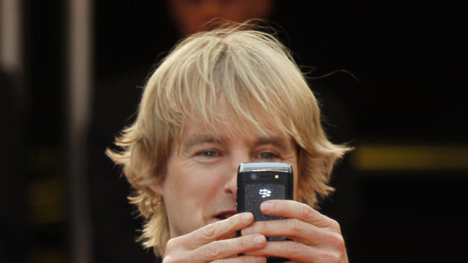 Actor Owen Wilson takes a photo as he arrives for the screening of Midnight in Paris and the opening ceremony, at the 64th international film festival, in Cannes, southern France, Wednesday, May 11, 2011. (AP Photo/Joel Ryan)