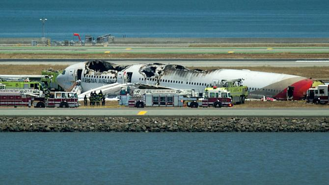 Fire crews respond to the scene where Asiana Flight 214 crashed at San Francisco International Airport on Saturday, July 6, 2013, in San Francisco. (AP Photo/Noah Berger)