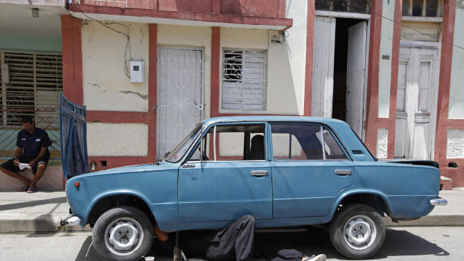 In this photo taken Monday April 23, 2012,  a man climbs under the engine of his Russian-made car while repairing it in Bayamo, Cuba.  Since cars are expensive, many of the ones on the streets have old bodies but have engines that have been repaired and replaced multiple times. (AP Photo/Kathy Willens)