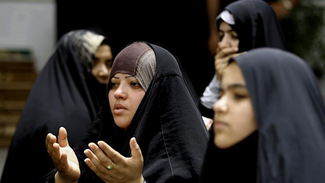 In this Tuesday, June 4, 2013 photo, Shiite women pray at the Imam Moussa al-Kadhim shrine at Kazimiyah district of Baghdad, Iraq. Hatreds between Shiites and Sunnis are now more virulent than ever in the Arab world because of Syria's brutal civil war. Hard-line clerics and politicians on both sides have added fuel, depicting the fight as essentially a war of survival for their sect. (AP Photo/ Karim Kadim)