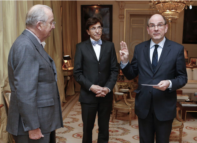 Belgium's newly appointed Minister of Finance Koen Geens, right, takes the oath of office in front of Belgium's King Albert II, left, and Belgium's Prime Minister Elio Di Rupo, center, at the Royal Pa