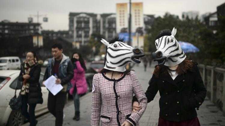 Participants wearing zebra head masks wander down a street as part of an artistic performance in Chongqing