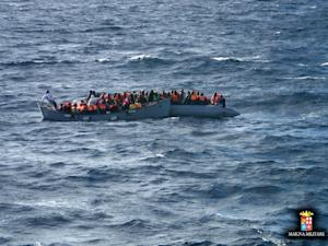 Migrants sit in a boat during a rescue operation off…