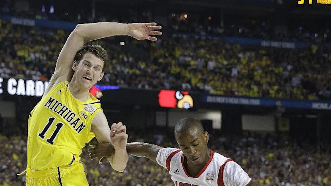 Louisville guard Russ Smith (2) and Michigan guard Nik Stauskas (11) work for a loose ball during the first half of the NCAA Final Four tournament college basketball championship game Monday, April 8, 2013, in Atlanta. (AP Photo/David J. Phillip)