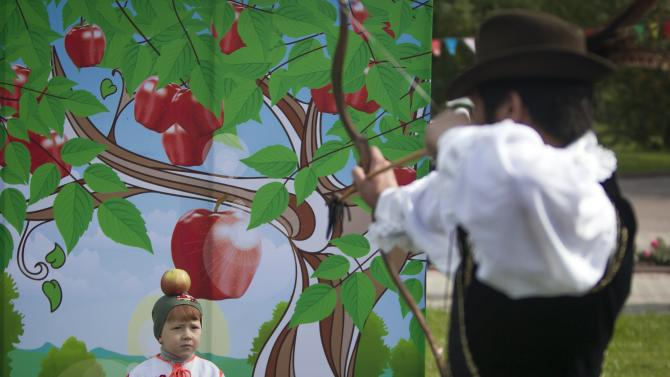 Boy poses for a picture as an artist pretends to shoot an apple off his head during the Apple Festival at City Day celebrations in Almaty