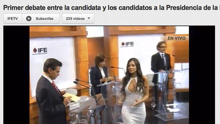 In this screen grab taken from Mexico's Federal Electoral Institute's YouTube channel, Julia Orayen, second from right, carries a box to presidential candidates containing paper for them to take to assign their speaking order at the start of a presidential candidate debate in Mexico City, Sunday, May 6, 2012. The Federal Election Commission, which organized the debate, said an independent producer had hired the former model, and acknowledged that her dress choice was a mistake. (AP Photo/IFETV via YouTube)