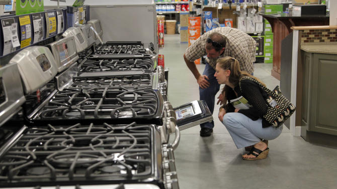 In this Monday, Sept. 10, 2012 photo Brian Gibson, top right, and his wife Elizabeth Gibson, below right, both of Framingham, Mass., examine stoves at a Lowe's store location in Framingham.  U.S. companies remained cautious in September and held back on orders for long-lasting manufactured goods that signal investment plans. (AP Photo/Steven Senne)