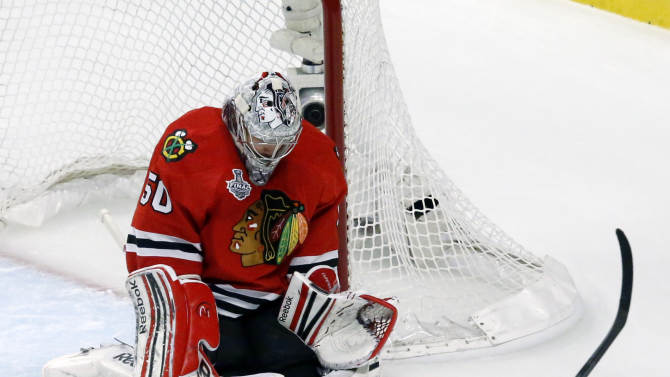 Chicago Blackhawks goalie Corey Crawford (50) makes a save on a shot by Boston Bruins center David Krejci (46) during the first period of Game 1 in their NHL Stanley Cup Final hockey series,Wednesday, June 12, 2013 in Chicago. (AP Photo/Charles Rex Arbogast)
