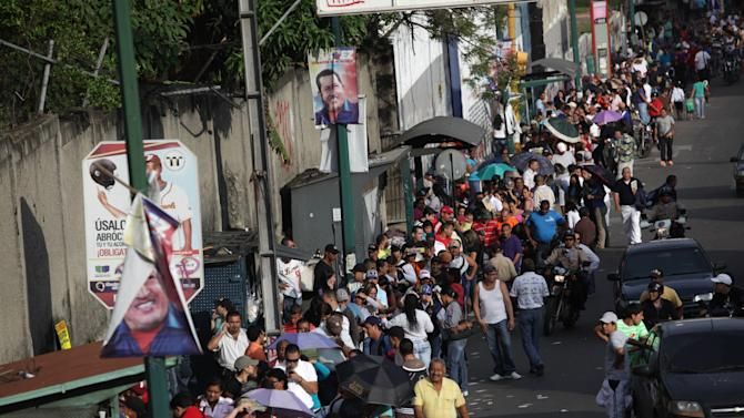 Residents wait in line at a polling station to vote in the presidential election in the Catia neighborhood of Caracas, Venezuela, Sunday, Oct. 7, 2012. President Hugo Chavez is running against opposition candidate Henrique Capriles. (AP Photo/Rodrigo Abd)