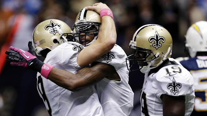 New Orleans Saints quarterback Drew Brees (9) celebrates with wide receiver Marques Colston (12) as wide receiver Devery Henderson (19) stands by after a touchdown pass in the second half of an NFL football game against the San Diego Chargers at Mercedes-Benz Superdome in New Orleans, Sunday, Oct. 7, 2012. (AP Photo/Dave Martin)