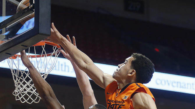 Texas Tech's Toddrick Gotcher drives against Oklahoma State's Jeffrey Carroll during an NCAA college basketball game in Lubbock, Texas, Saturday, Feb. 28, 2015. (AP Photo/Lubbock Avalanche-Journal, Shannon Wilson)