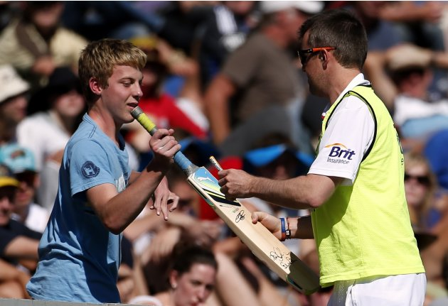 England cricket team spinner Swann autographs a bat for a boy in the crowd during the second day of the first test against New Zealand at the University Oval in Dunedin