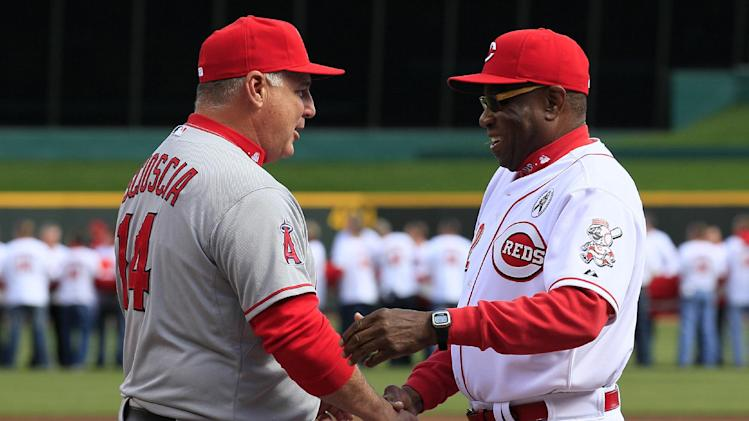 Los Angeles Angels manager Mike Scioscia (14) shakes hands with Cincinnati Reds manager Dusty Baker at the start of a major league baseball game, Monday, April 1, 2013, in Cincinnati. (AP Photo/Al Behrman)