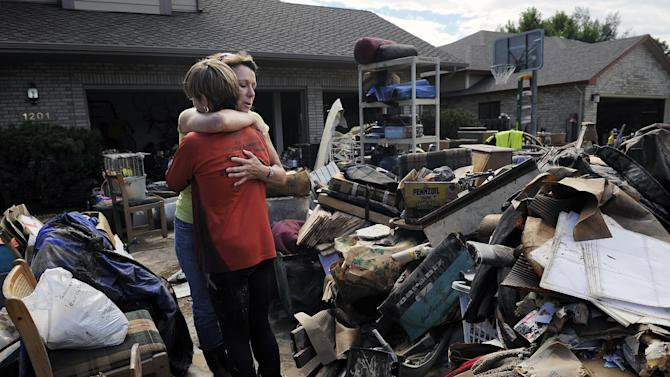 Homeowner Chris Ringdahl, left, is comforted by family friend Katherine MacIntosh, right, in front of her possessions as they cleanup from the floodwaters in Longmont, Colo., on Monday, Sept. 16, 2013. Floodwaters have affected a 4,500 square-mile section of the state inundating entire neighborhoods and destroying bridges and roads. (AP Photo/Chris Schneider)