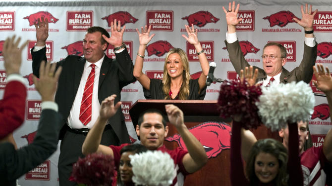 "Arkansas football coach Bret Bielema, top left, his wife, Jen, center, and athletic director Jeff Long, right, ""call the hogs"" during a news conference to announce Bielema's hire in Fayetteville, Ark., Wednesday, Dec 5, 2012. Bielema, who will be paid $3.2 million annually for six years, replaces interim coach John L. Smith, who was hired after Bobby Petrino was fired in April. (AP Photo/April L. Brown)"