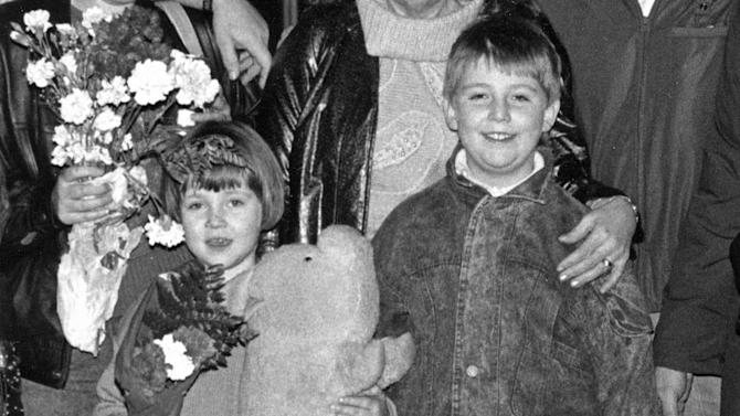In this image provided by Anna Tabakh, she and her older brother, Ilya, stand with their family after arriving at the Kansas City, Mo. airport in December 1990, a year before the collapse of the Soviet Union. At age 5, Anna didn't know a word of English, en route with her parents from the Soviet Union to a new home in Kansas City, Mo. The beginning was traumatic, she says, now 27, but the transition to American life was relatively smooth - a result that some social scientists would say was partly due to her age. (AP Photo/Anna Tabakh)