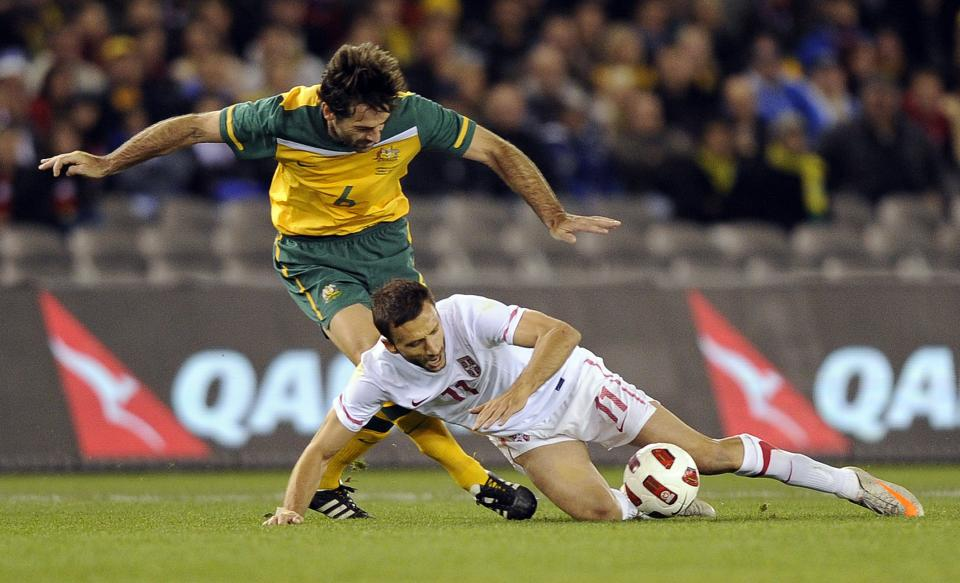 Serbia's Bryan Habana, right, and Australia's Sasa Ognenovski compete for the ball during their friendly soccer match in Melbourne, Australia, Tuesday, June 7, 2011. (AP Photo/Andrew Brownbill)