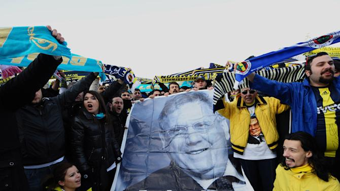 """FILE - In this Monday, Feb. 20, 2012 file photo Fenerbahce supporters gather outside a Turkish court house in support of 93 suspects, including the club's jailed president Aziz Yildirim, depicted in poster, during a hearing into a soccer match-fixing case in Istanbul, Turkey. Yildirim, 60-year-old tycoon was convicted in July of """"forming and leading a criminal gang"""" that rigged four games and offered payments to players or rival club officials to fix three others _ all so Fenerbahce could stay in the Champions League, a benefit the club estimated to be worth $58.5 million a year. He is appealing his conviction, maintaining his innocence. (AP Photo, File)"""