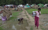 An internally displaced Rohingya woman carries water at a camp for displaced Rohingya in Sittwe, northwestern Rakhine State, Myanmar, ahead of the arrival of Cyclone Mahasen, Wednesday, May 15, 2013. A massive evacuation to clear low-lying camps ahead of the cyclone has run into a potentially deadly snag as members of the displaced Rohingya minority living there have refused to leave because they don't trust Myanmar authorities. (AP Photo/Gemunu Amarasinghe)