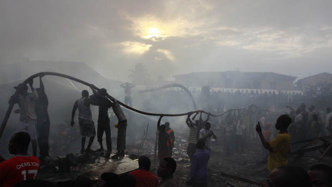 People gather at the site of a plane crash in Lagos, Nigeria, Sunday, June 3, 2012. A passenger plane carrying more than 150 people crashed in Nigeria's largest city on Sunday, government officials said. Firefighters pulled at least one body from a building that was damaged by the crash and searched for survivors as several charred corpses could be seen in the rubble.(AP Photo/Sunday Alamba)