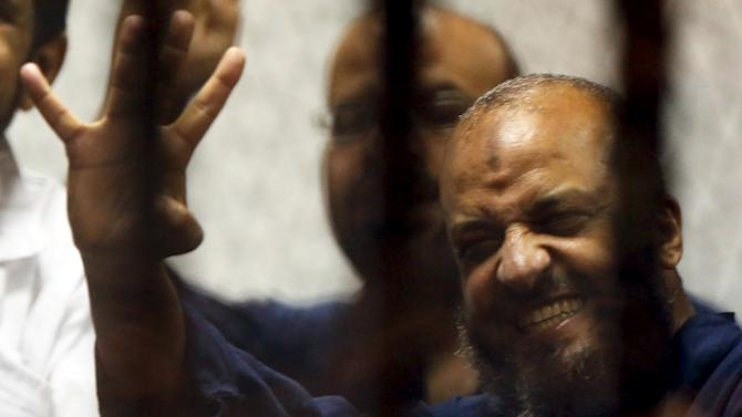 Muslim Brotherhood's senior member Mohamed El-Beltagy laughs and waves the Rabia sign, behind bars with other Muslim Brotherhood members at a court in the outskirts of Cairo