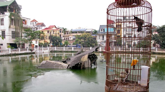 A bird sits in a cage overlooking the engine of an American B-52 bomber in a lake in Hanoi, Vietnam, on Friday, March 29, 2013.  The plane was was shot down during the Vietnam War, and the engine fell into the lake. Friday is the 40th anniversary of the American troop pullout of Vietnam. (AP Photo/Chris Brummitt)