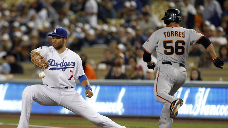 Los Angeles Dodgers first baseman James Loney (7) doesn't hold on to the ball as San Francisco Giants' Andres Torres (56) reaches safely on an error by third baseman Aaron Miles during the first inning of a baseball game in Los Angeles, Tuesday, Sept. 20, 2011. (AP Photo/Alex Gallardo)