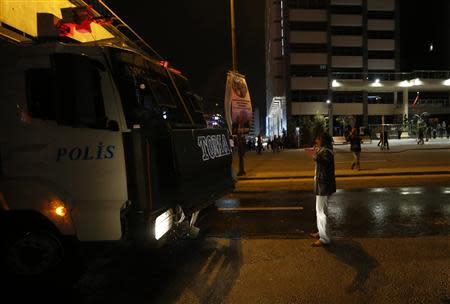 A man stands in front of an armoured police vehicle as he tries to stop it during a protest against Turkey's PM Erdogan in Ankara